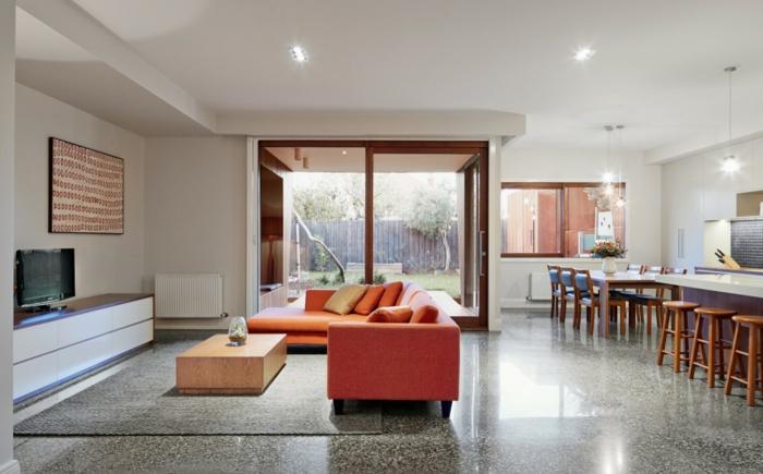 modern einrichten offener wohnplan oranges sofa grauer teppich küche absondern
