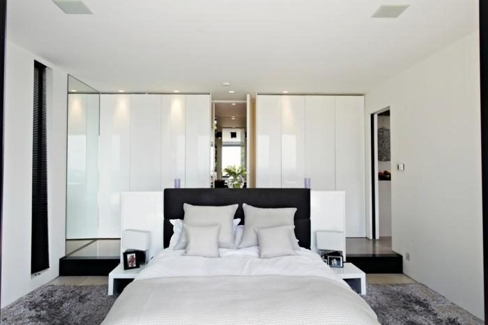 schlafzimmer weiß grauer teppich moderner kleiderschrank schwarzes bettkopfteil