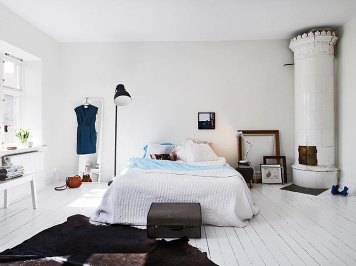 weißes schlafzimmer rustikaler kamin holzboden fellteppich