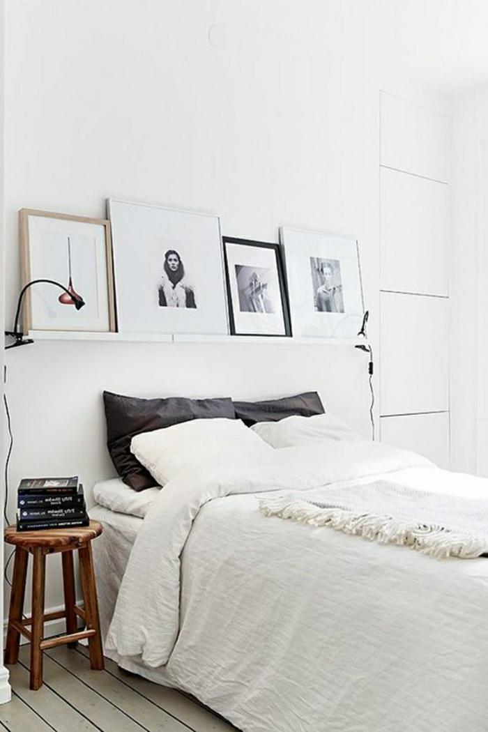 weißes schlafzimmer weiße wände wandregal bilder schwarze dekokissen