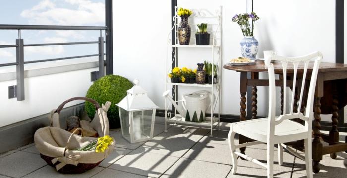 balkon gestalten balkonmöbel balkonpflanzen frühlingsblumen metallenes regal holztisch stuhl laterne korb