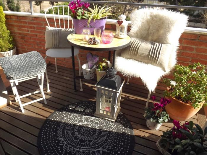 balkon gestalten balkonmöbel balkonpflanzen keramiktöpfe runder teppichläufer laternen runder tischstühle hocker