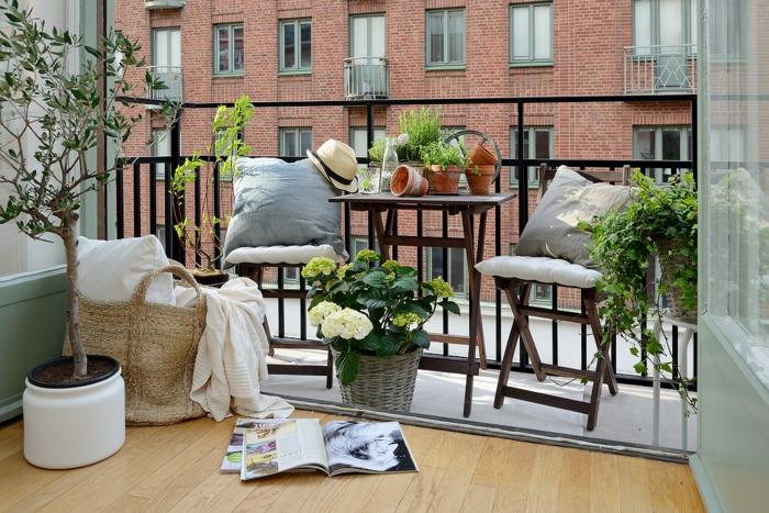 balkon gestalten balkonmöbel klappstühle tisch blumentöpfe geflochtene blumentöpfe olivenbaum hortensien