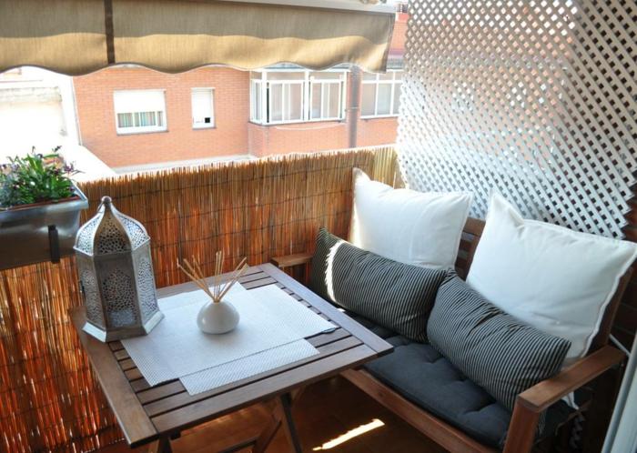 balkon gestalten balkonmöbel metallene laterne couch tisch kissen auflage sitzschutz stroh