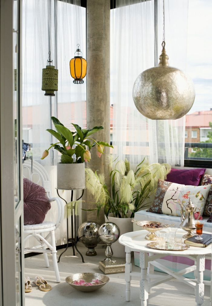 balkon gestalten balkonmöbel orientalisch pendelleuchte laternen runder tisch sofa kissen
