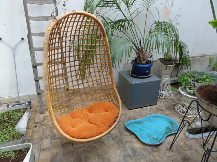 balkongestaltung hängesessel oranges sitzkissen rattanmöbel
