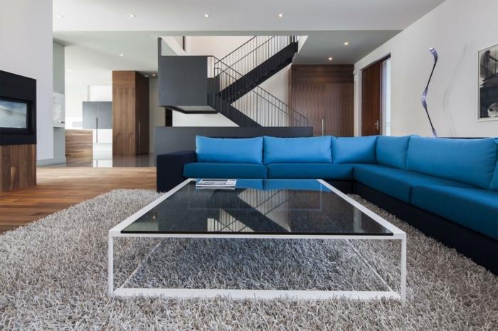 blaues sofa ecksofa gläserner couchtisch beiger teppich