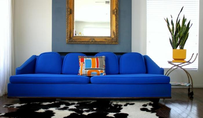 blaues sofa fellteppich weiße gardinen wanddeko