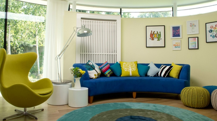 blaues sofa gelber sessel runder teppich farbig hocker weiße gardinen