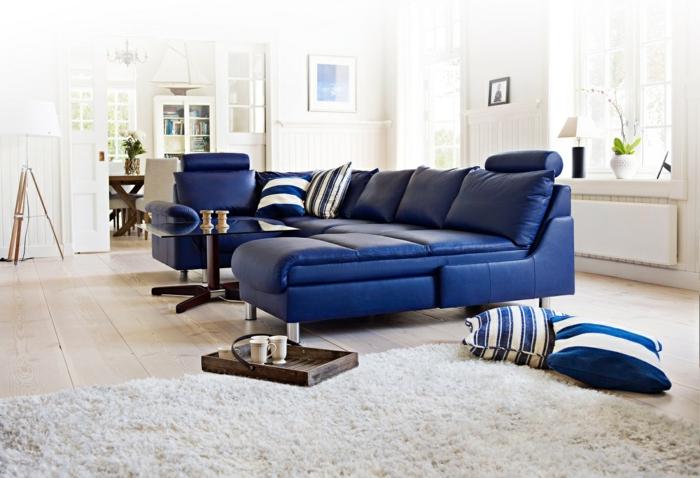 blaues sofa leder weißer teppich holzboden bodenkissen
