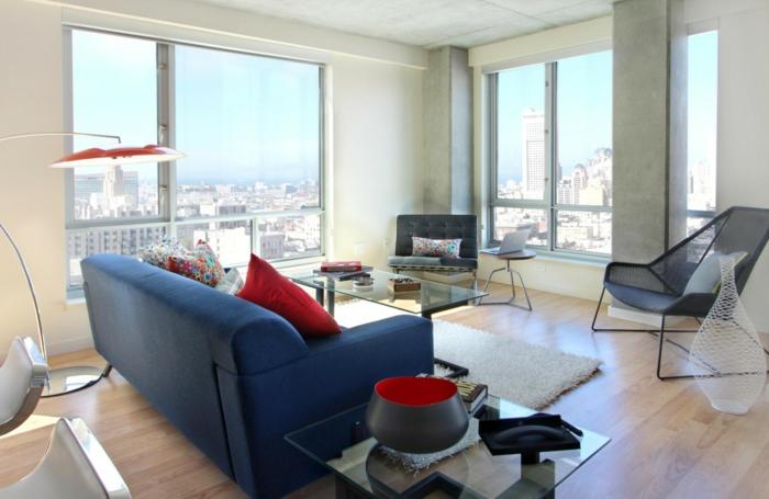 blaues sofa rote akzente weißer teppich gläserner couchtisch panoramafenster