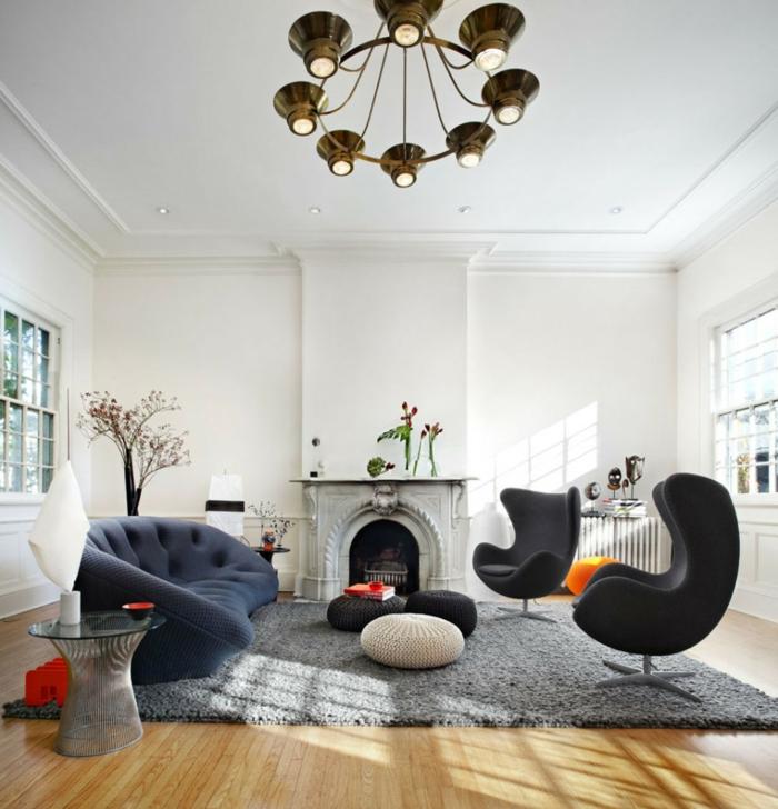 sofa blau ausgefallen dunkelblau grauer teppich schwarze sessel feuerstelle weiße wände