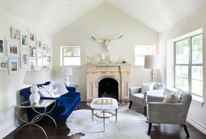sofa blau fellteppich kamin weiße wände wanddeko kerzen
