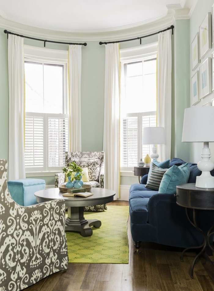 sofa blau grüner teppich holzboden blumen helle gardinen