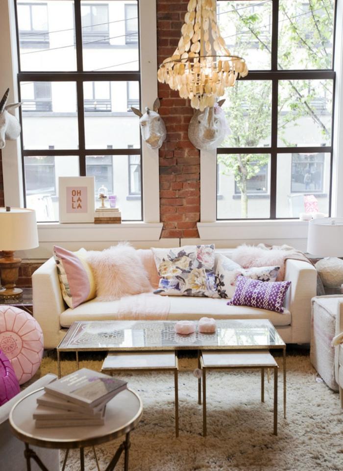 wandfarbe rosa ziegelsteinwand kronleuchter weißes ledersofa dekokissen hochflor teppich