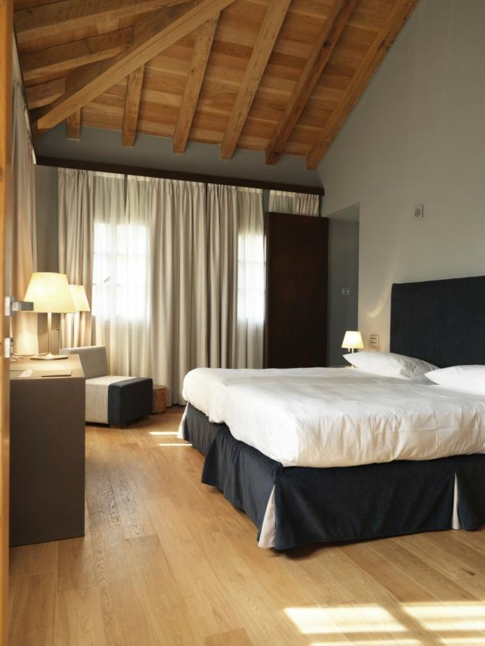 wohnideen schlafzimmer weiße wände schwarzes bettkopfteil holzbalken