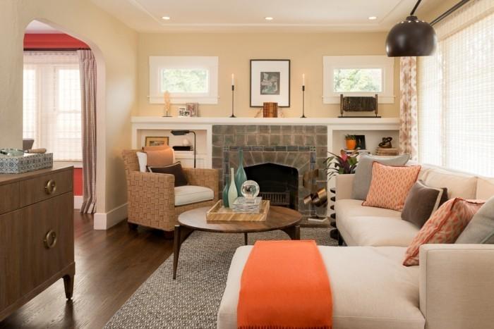 schönes wohnzimmerorange akzente stilvoller teppich kamin beige wände