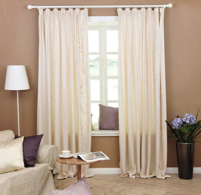 wohnideen wohnzimmer wände beige helle gardinen blumen lila dekokissen
