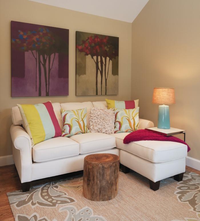 wohnzimmer beige helle wände weißes sofa rustikaler couchtisch floraler teppich