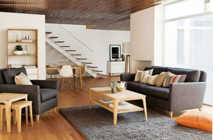 wohnzimmer grau grauer teppich dunkle möbel holztisch dekokissen