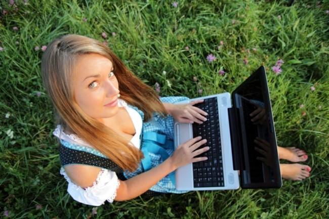 Dirndl in Blumenwiese mit Laptop von oben