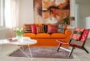 wandbilder-wohnzimmer-oranges-sofa-dekokissen-teppich-holzboden