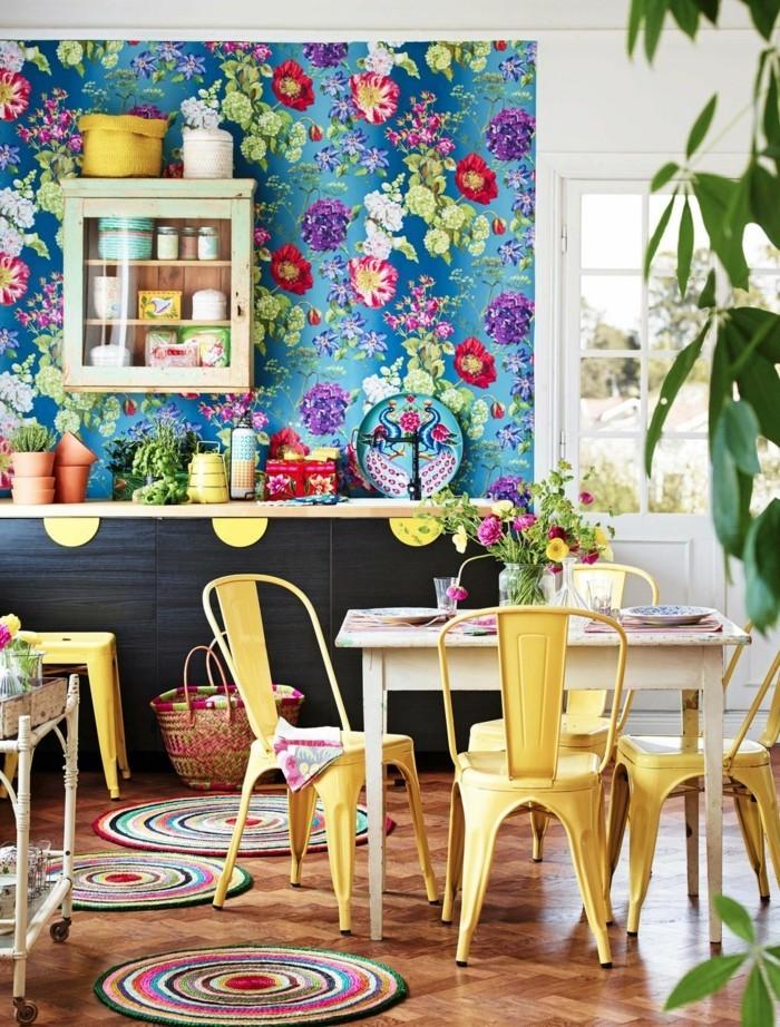 küchendesign mit floralen wandmustern und gelben küchenstühlen