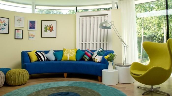 teppich rund blaues sofa farbige dekokissen grüner sessel weiße beistelltische