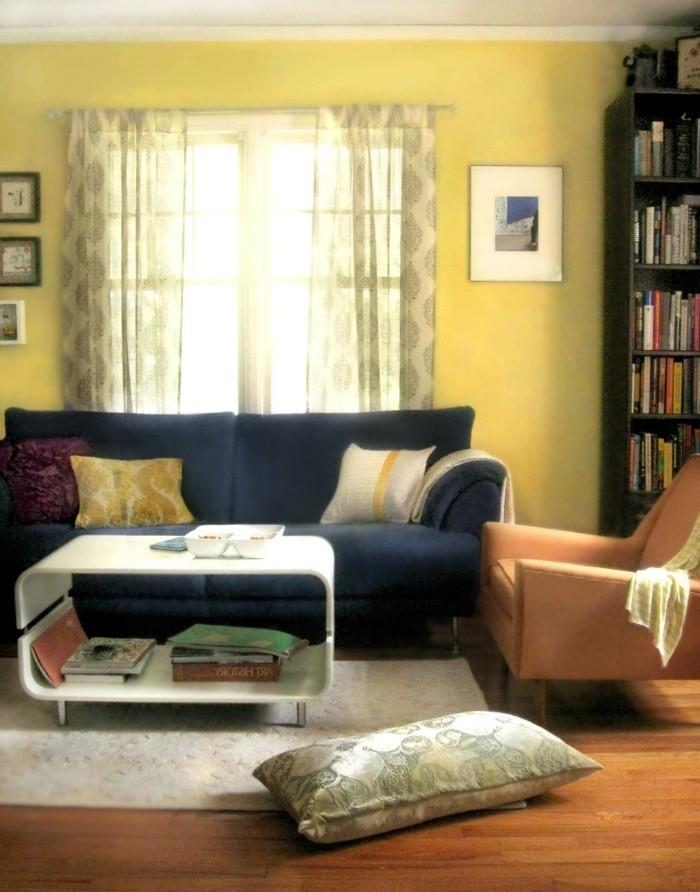 wohnungseinrichtung hellgelbe wandfarbe dunkles sofa weißer teppich