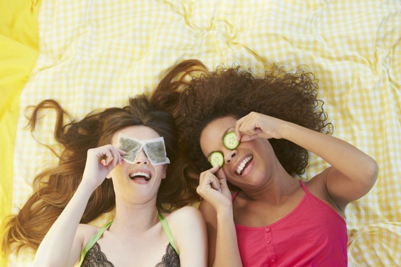 Two Female Friends Lying On Bed Using Beauty Treatments Playing Around