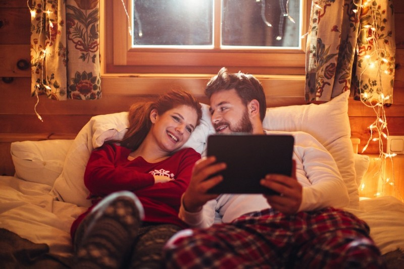 Couple lying on cozy bed in wooden cabin. Wearing Christmas pajamas. Together watching movie on digital tablet. Enjoying in the warmth of their home for Christmas. Room is decorated with festive string lights. Austrian Alps. Evening or night with beautiful yellow lights lightning the scenes.