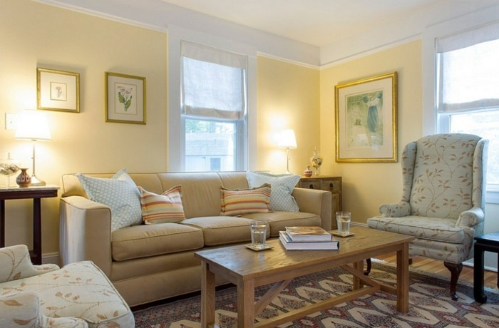 wohnzimmer wand muster:wohnzimmer gestaltung hellgelbe wand creme sofa viele muster wanddeko