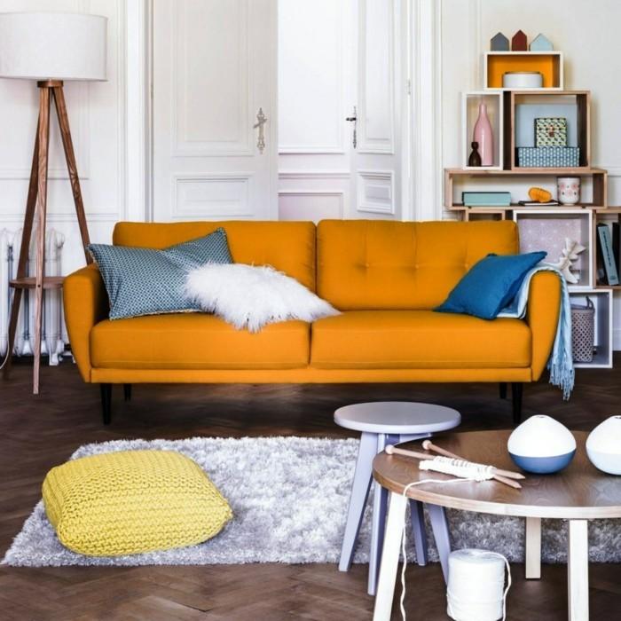 wohnideen wohnzimmer oranges sofa heller teppich dekokissen