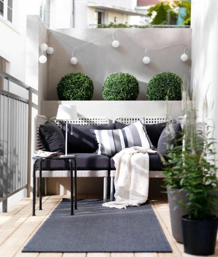 balkon gestalten balkonmöbel rattanmöbel sofa sitzbank hocker beistelltisch lichterkette buchsbaum holzdielen