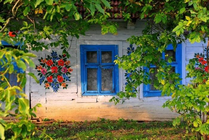 hausfassade gestalten zalipie blaue fenster gartenpflanzen blumendeko