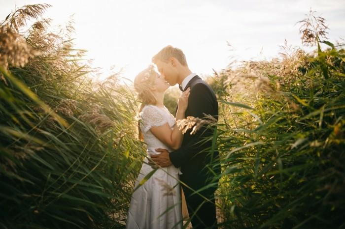 braut und bräutigam küssen sich im maisfeld