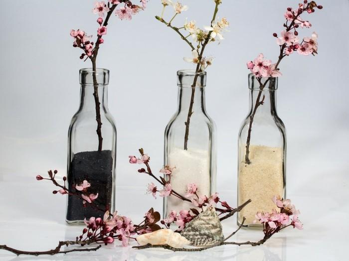 glasflaschen mit frühlingszweigen blüten frühlingsdekoration