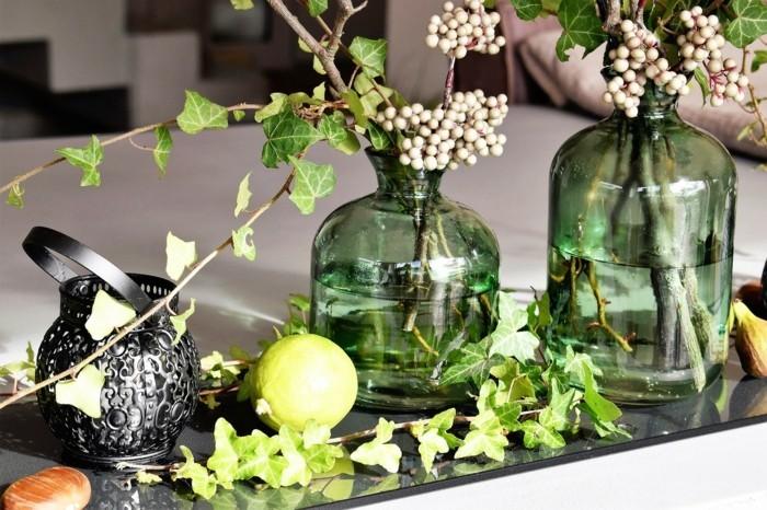 grüne glasvasen mit zweigen dekoriert