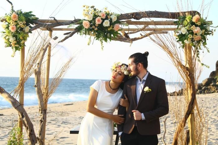 hochzeit am strand mit rosenbogen braut und bräutigam