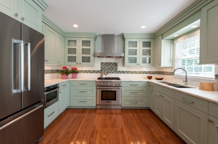 moderne küche in u form mit hellgrünen küchenschränken und boden mit holzoptik