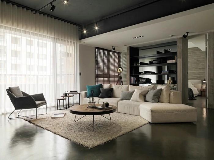 modernes wohnen geräumiges wohnzimmer mit rundem kaffeetisch und teppich