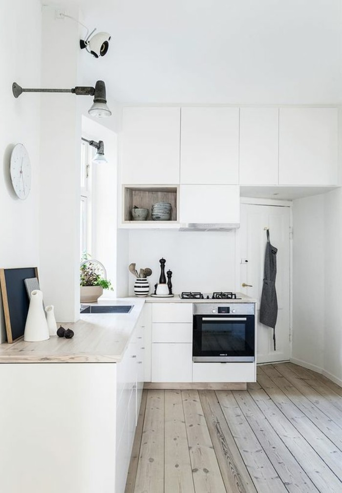weiße küche mit holzboden und wanduhr