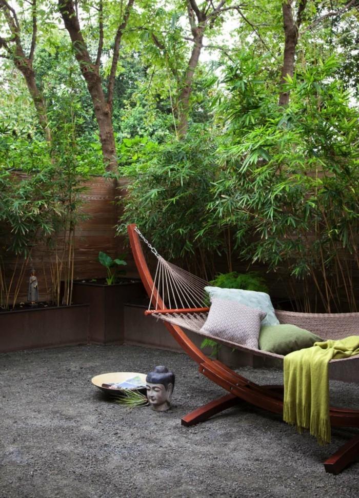 gartenmöbel hängematte im hinterhof und reichliche gartenbepflanzung