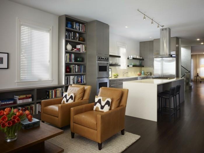 offene küche mit grauen küchenschränken und wohnbereich mit ledersesseln