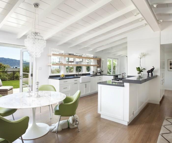 offene küche mit weißen möbelstücken und grünen akzenten