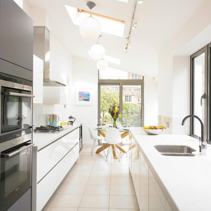 offene küche mit weißer einrichtung und creme bodenfliesen