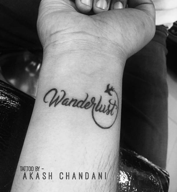 wanderlust tattoo motiv schriftzug handgelenk