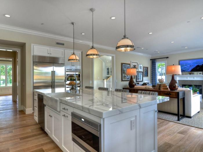 wohnküche mit weißer kücheninsel und pedelleuchten