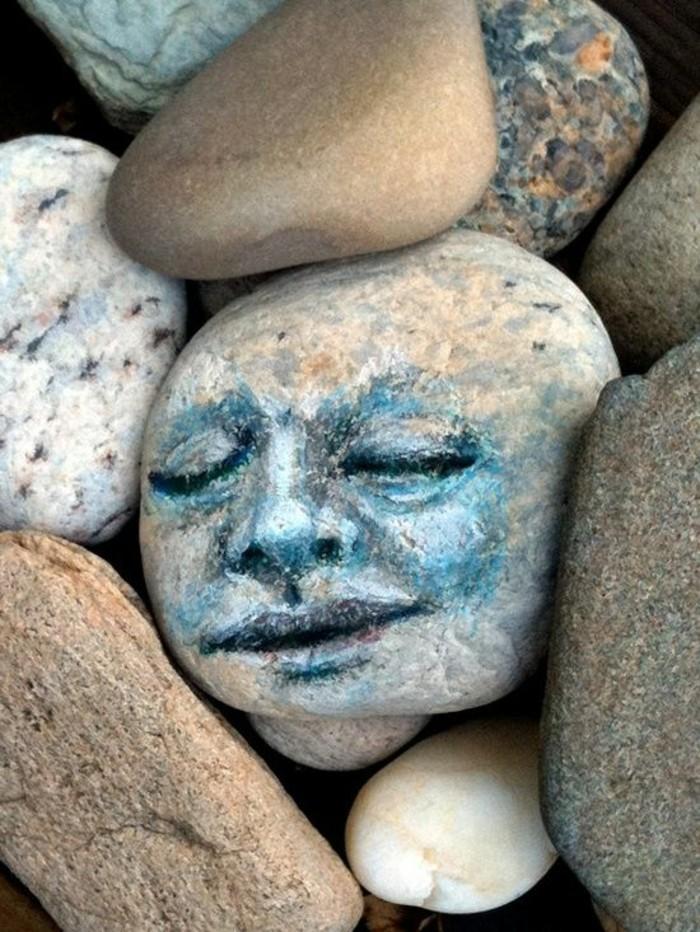 kunst mit steinen gesicht auf flussstein malen