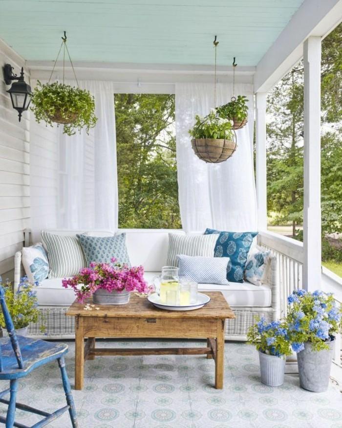 veranda mit vielen blumetöpfen hölzernem tisch und rattansofa